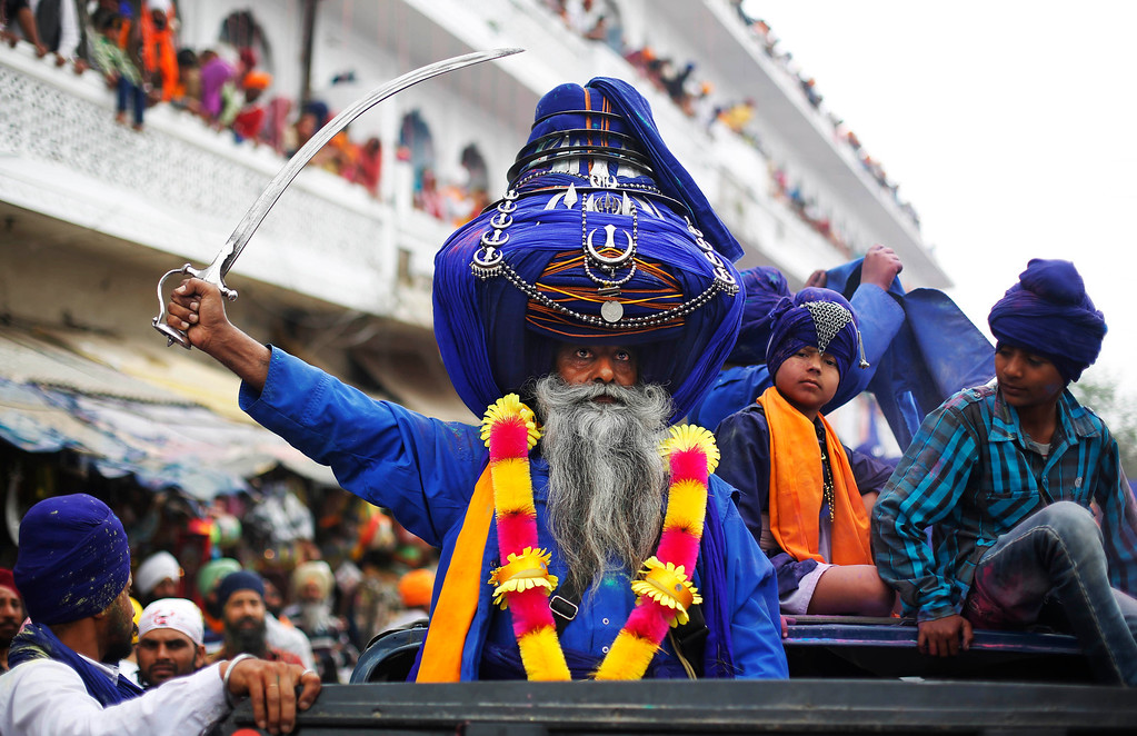 . Sikh warrior Major Singh, wearing a 425 meters long turban, brandishes a sword as he participates in a religious procession during the annual fair of \'Hola Mohalla\'  in Anandpur Sahib, in the northern Indian state of Punjab, Monday, March 17, 2014. Believers from various parts of northern India collect at the religious fair to celebrate the festival of Holi in a tradition set by the tenth Sikh guru Guru Gobind Singh in the seventeenth century. Nihangs, or Sikh warriors, display their martial skills and attire during the fair, believed to be maintained in the exact tradition as set by the Guru. (AP Photo/Altaf Qadri)