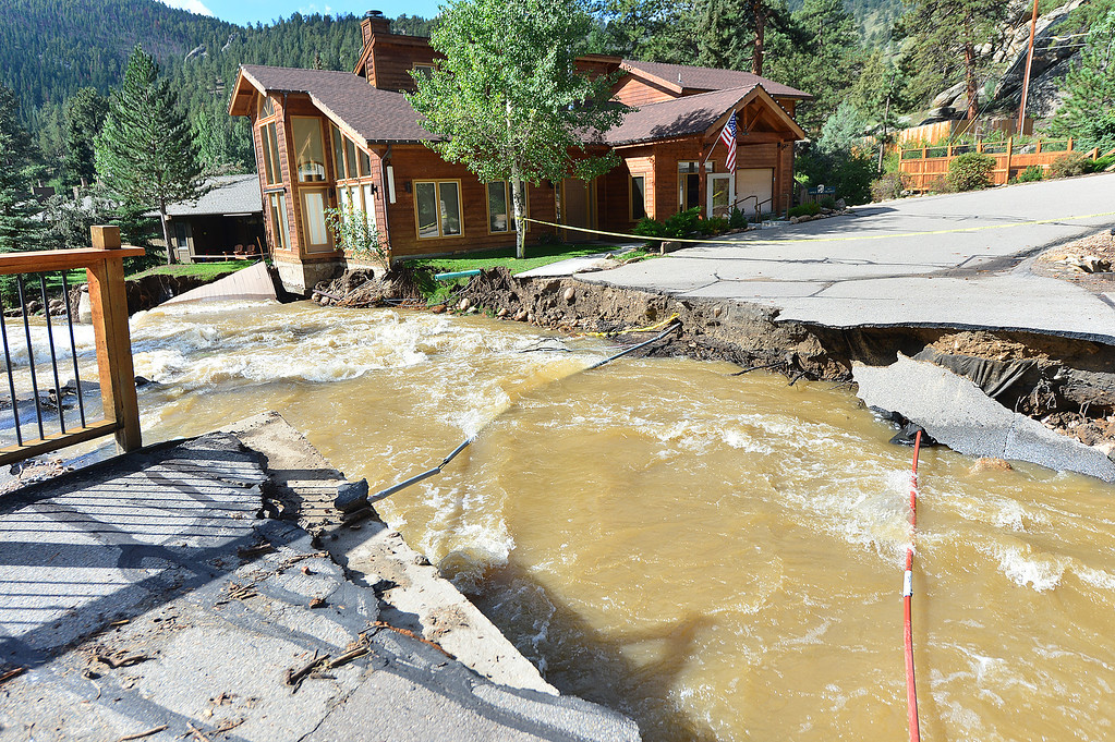 . Brown water rushes past a gap in a bridge on Monday, Sept 16, 2013 created by the weekend flooding along Fall River Road. A lot of infrastructure was damaged in the flooding. Walt Hester/Estes Park Trail-Gazette