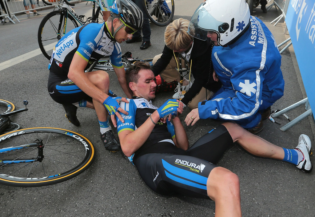 . A doctor, right, and a teammate tend to Portugals\' Tiago Machado after he crashed during the seventh stage of the Tour de France cycling race over 234.5 kilometers (145.7 miles) with start in Epernay and finish in Nancy, France, Friday, July 11, 2014. (AP Photo/Fred Mons, Pool)