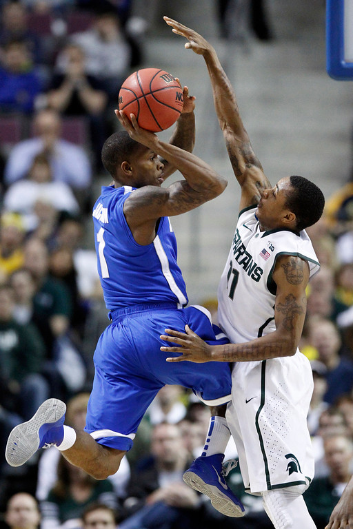 . Memphis guard Joe Jackson (1) is forced to pass the ball against the defense from Michigan State guard Keith Appling (11) in the first half of a third-round game of the NCAA college basketball tournament Saturday, March 23, 2013, in Auburn Hills, Mich. (AP Photo/Duane Burleson)
