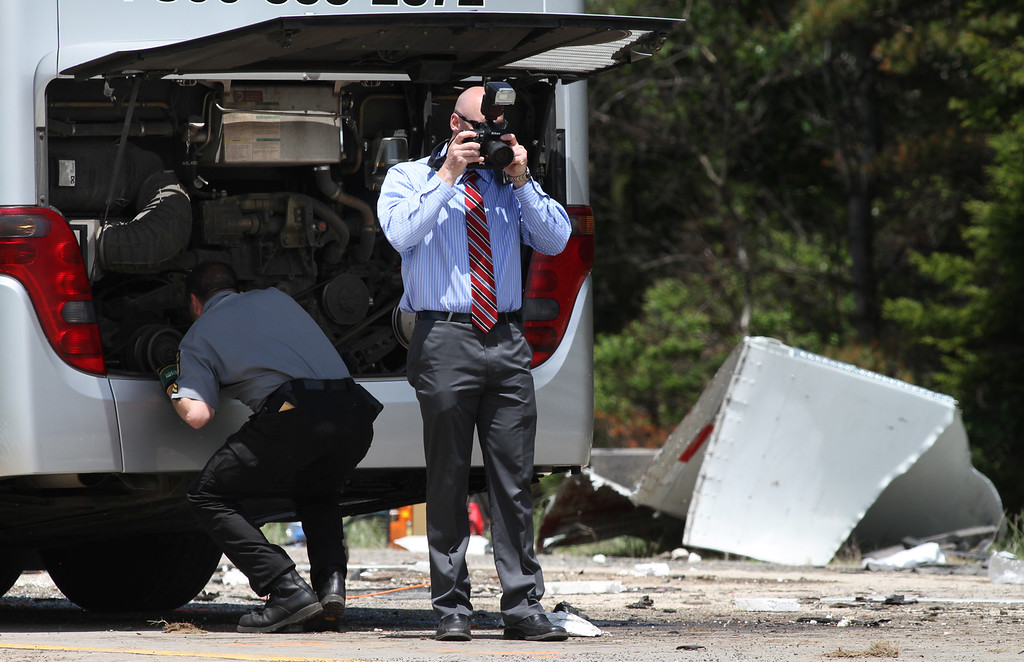 . Authorities investigate the scene of a fatal collision between a tractor-trailer and a tour bus on Interstate 380 near Tobyhanna, Pa., Wednesday, June 3, 2015. Multiple people were killed and more than a dozen were sent to hospitals. (Jake Danna Stevens/The Times & Tribune via AP)