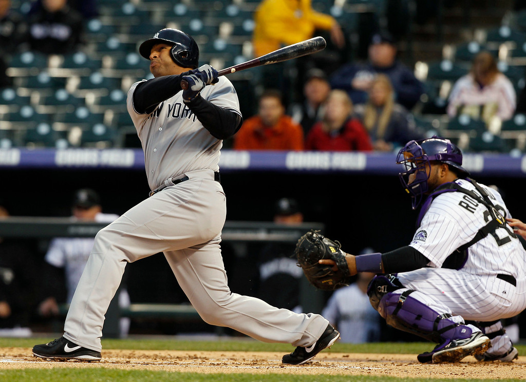 . New York Yankees\' Vernon Wells, left, follows the flight of his two-run home run with Colorado Rockies catcher Wilin Rosario in the first inning of a baseball game in Denver on Wednesday, May 8, 2013. (AP Photo/David Zalubowski)