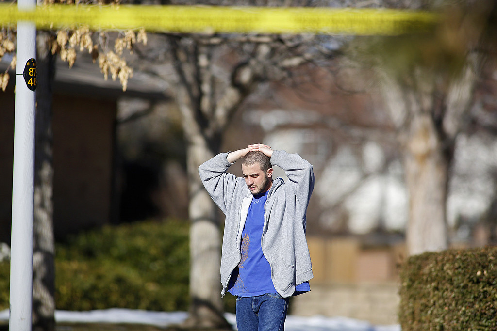 . A neighbor takes in the scene at a town home where four people were killed Saturday morning including the gunman who held police at bay for several hours at the complex January 5, 2013 in Aurora, Colorado. Aurora SWAT team members shot a gunman after he went to a second-floor window and fired at police. The gunman also allegedly fatally shot two men and a woman that he had taken hostage. One woman managed to escape from an upstairs back window, ran from the home and called police just before 3 a.m., said Cassidee Carlson, Aurora police spokeswoman.  (Photo by Marc Piscotty/Getty Images)