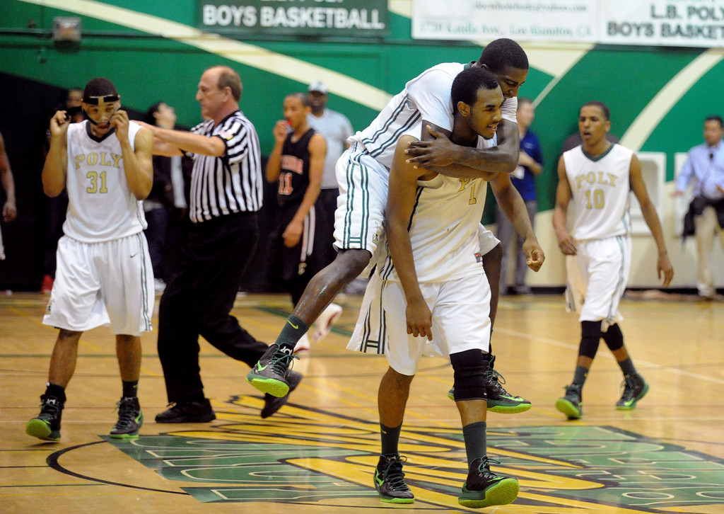 . 02-26-2012--(LANG Staff Photo by Sean Hiller)-Etiwanda beat Long Beach Poly 59-55 in Tuesday\'s CIF Southern Section Division 1AA semifinal boys basketball game at Long Beach Poly High School. Jordan Bell jumps on to Roschon Prince after Prince tied the game to send it to overtime.
