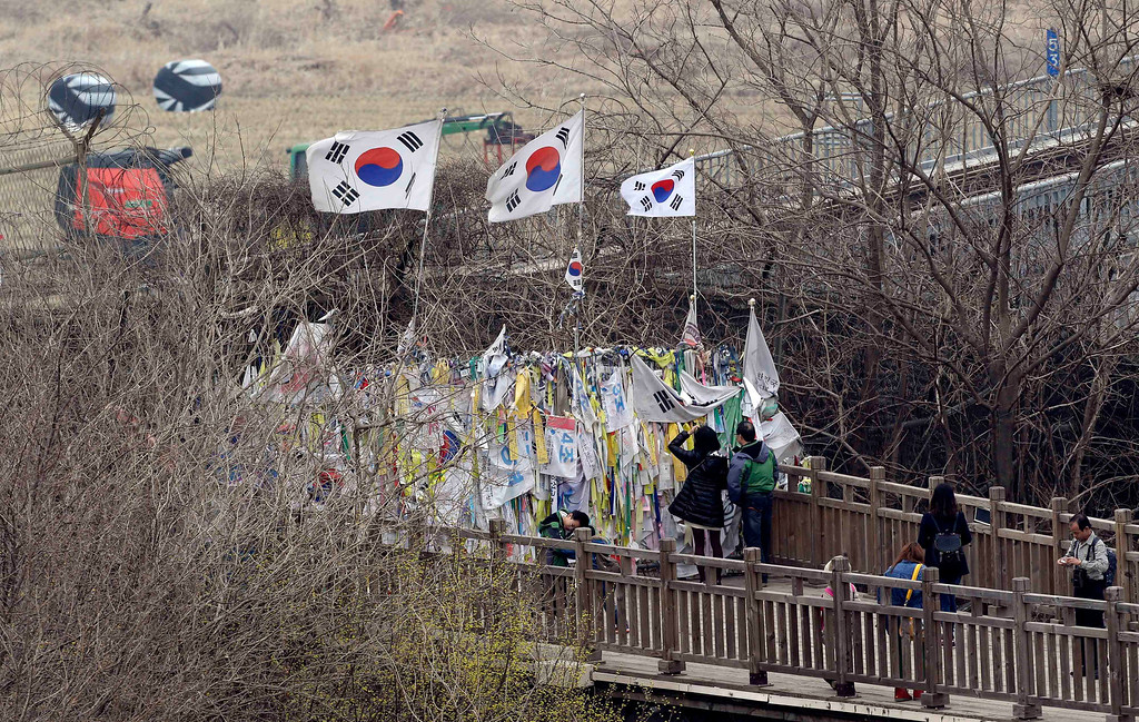 """. South Korean national flags flutter on a wire fence, where ribbons are hanging with messages wishing for reunification of the two Koreas, at the Imjingak Pavilion near the border village of Panmunjom, dividing the two Koreas since the Korean War, in Paju, north of Seoul, South Korea, Friday, April 5, 2013. After a series of escalating threats, North Korea has moved a missile with \""""considerable range\"""" to its east coast, South Korea\'s defense minister said Thursday. But he emphasized that the missile was not capable of reaching the United States and that there are no signs that the North is preparing for a full-scale conflict. (AP Photo/Lee Jin-man)"""