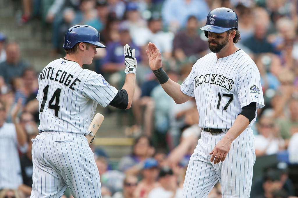 . Todd Helton #17 of the Colorado Rockies celebrates a fourth inning run with Josh Rutledge #14 during a game against the Arizona Diamondbacks at Coors Field on September 22, 2013 in Denver, Colorado.  (Photo by Dustin Bradford/Getty Images)