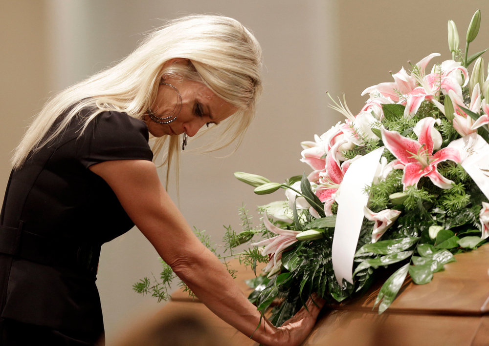 Description of . Jill Stancel places her hand on the casket of country music star Mindy McCready during the funeral ceremony at the Crossroads Baptist Church in Fort Myers, Fla., Tuesday, Feb. 26, 2013.  McCready committed suicide Feb. 17 at her home in Arkansas, days after leaving a court-ordered substance abuse program. (AP Photo/Alan Diaz)