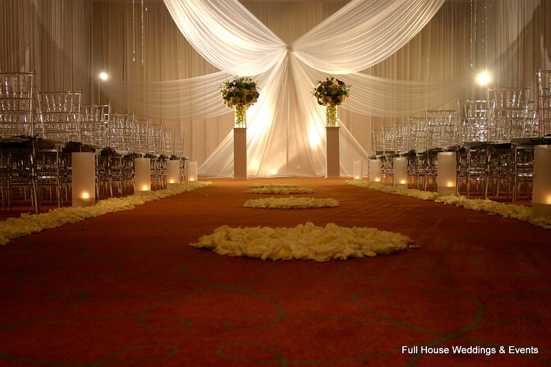 Wedding Ceremony inside the ballroom at Wyndham Crystal Palace Hotel. Ballroom draped entirely in white fabric. Altar arrangements set on columns.