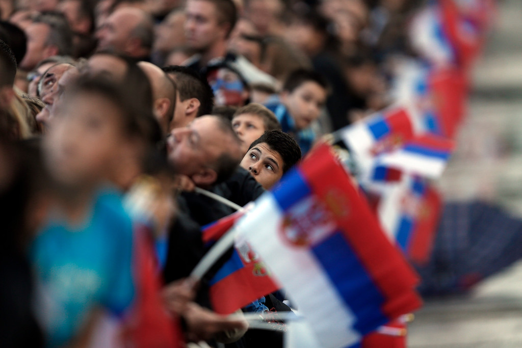 . A boy watches the Serbian army air display at a military parade in Belgrade, Serbia, Thursday, Oct. 16, 2014. Waving Russian and Serbian flags and displaying banners �Thank You Russia,� tens of thousands came to see the parade in Belgrade attended by Vladimir Putin, which marked the 70th anniversary of the liberation of the Serbian capital from the Nazi German occupation by the Red Army and Communist Yugoslav Partisans. (AP Photo/Marko Drobnjakovic)
