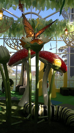 grub mushroom plant and tree sculptures on artificial turf and hanging leaves and butterfly