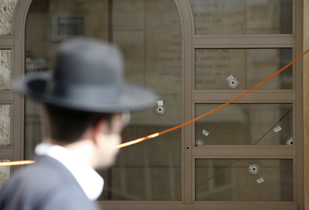 . An Ultra-orthodox Jewish man walks past synagogue, with bullet holes in the window, that was attacked by two Palestinians earlier in the morning in the ultra-Orthodox Har Nof neighborhood in Jerusalem on November 18, 2014.  AFP PHOTO/ JACK GUEZ/AFP/Getty Images