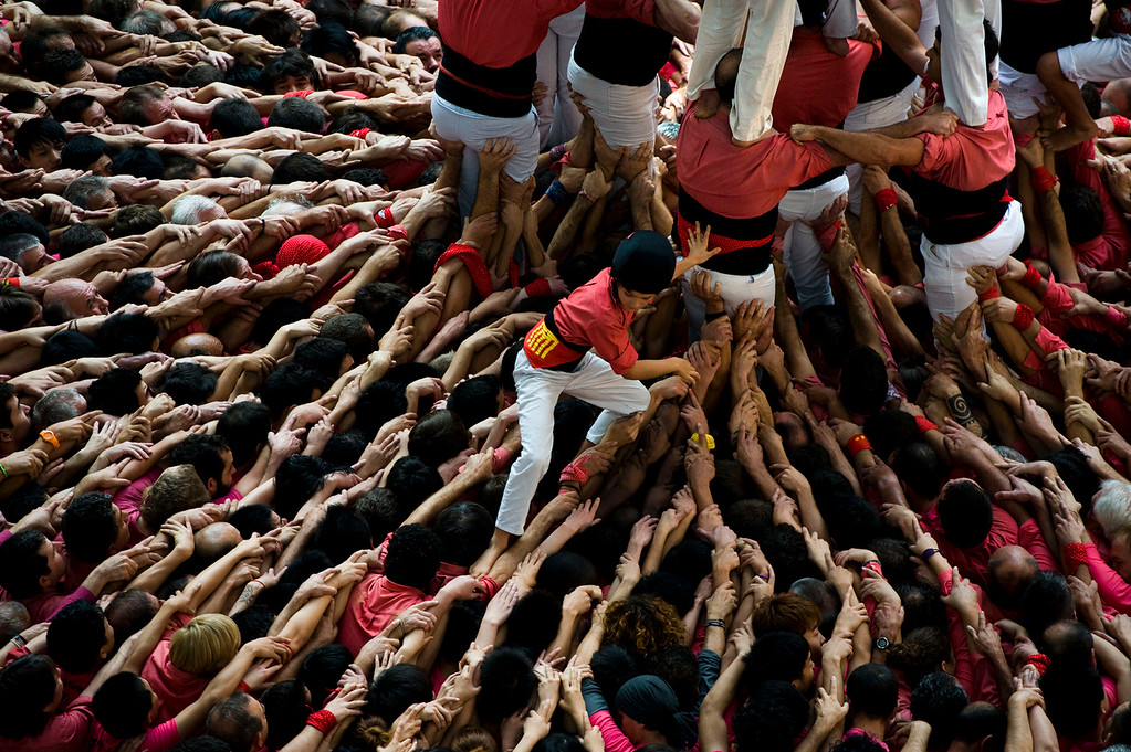 . A young member of the Colla \'Vella de Valls\' descends after bulding a human tower during the 24th Tarragona Castells Comptetion on October 7, 2012 in Tarragona, Spain. The \'Castellers\' who build the human towers with precise techniques compete in groups, known as \'colles\', at local festivals with aim to build the highest and most complex human tower. The Catalan tradition is believed to have originated from human towers built at the end of the 18th century by dance groups and is part of the Catalan culture.  (Photo by David Ramos/Getty Images)