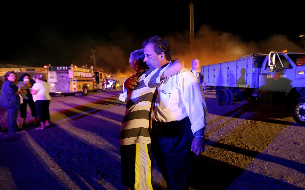 . New Jersey Gov. Chris Christie, right, is hugged by Michael Cisneros, 14, during a visit to the area hit by a massive fire on the Seaside Park boardwalk, Thursday, Sept. 12, 2013, in Seaside Park, N.J. The fire apparently started in an ice cream shop and spread several blocks down the boardwalk to neighboring Seaside Heights. (AP Photo/Julio Cortez)
