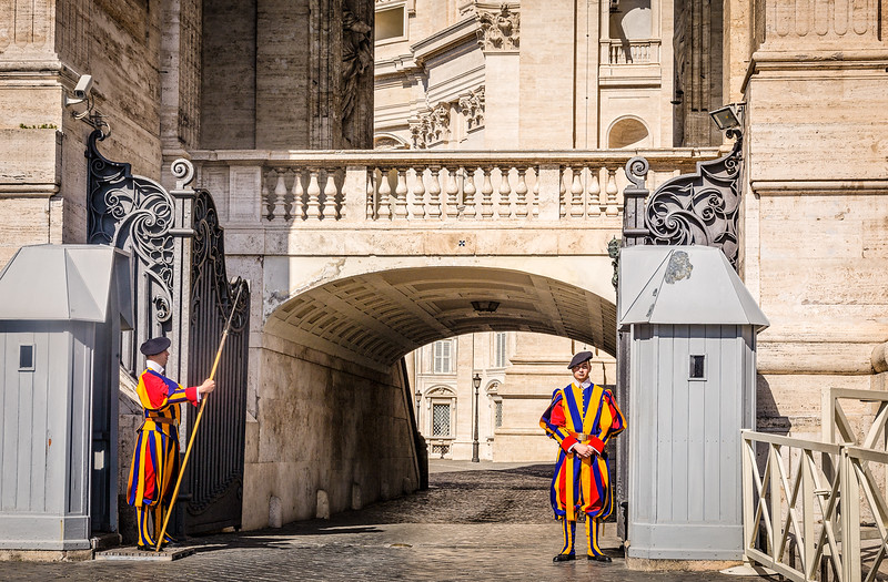 swiss guards in vibrant uniforms outside vatican entrance
