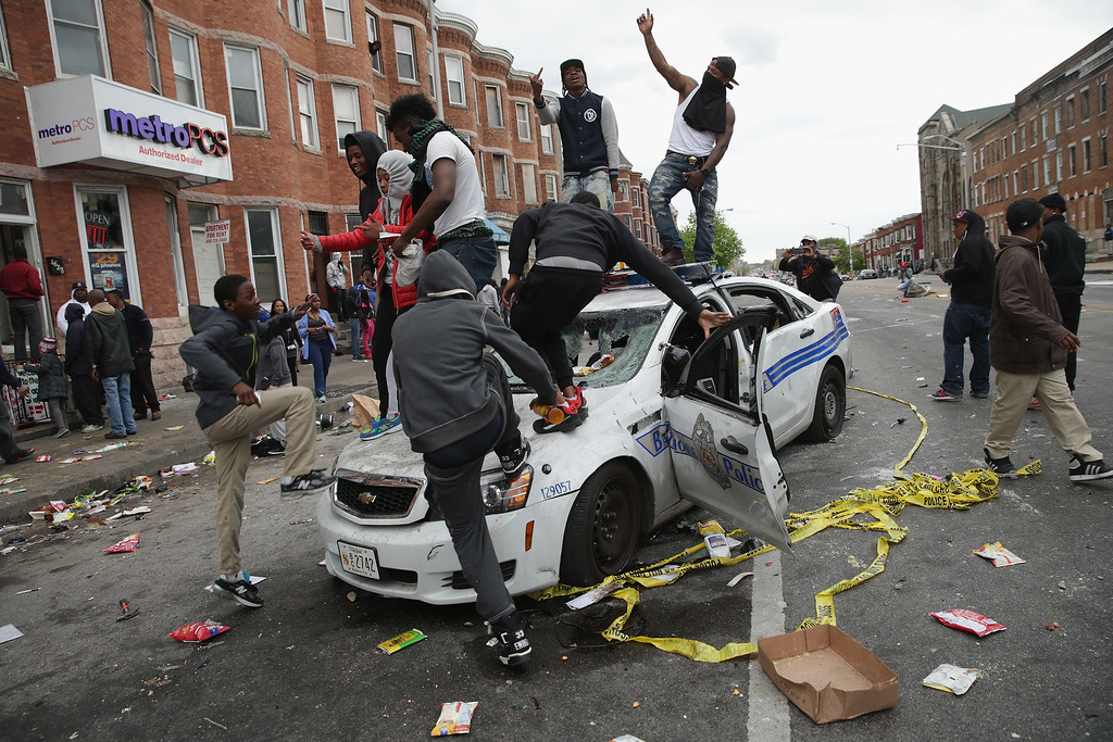 . Demonstrators climb on a destroyed Baltimore Police car in the street near the corner of Pennsylvania and North avenues during violent protests following the funeral of Freddie Gray April 27, 2015 in Baltimore, Maryland. Gray, 25, who was arrested for possessing a switch blade knife April 12 outside the Gilmor Homes housing project on Baltimore\'s west side. According to his attorney, Gray died a week later in the hospital from a severe spinal cord injury he received while in police custody.  (Photo by Chip Somodevilla/Getty Images)