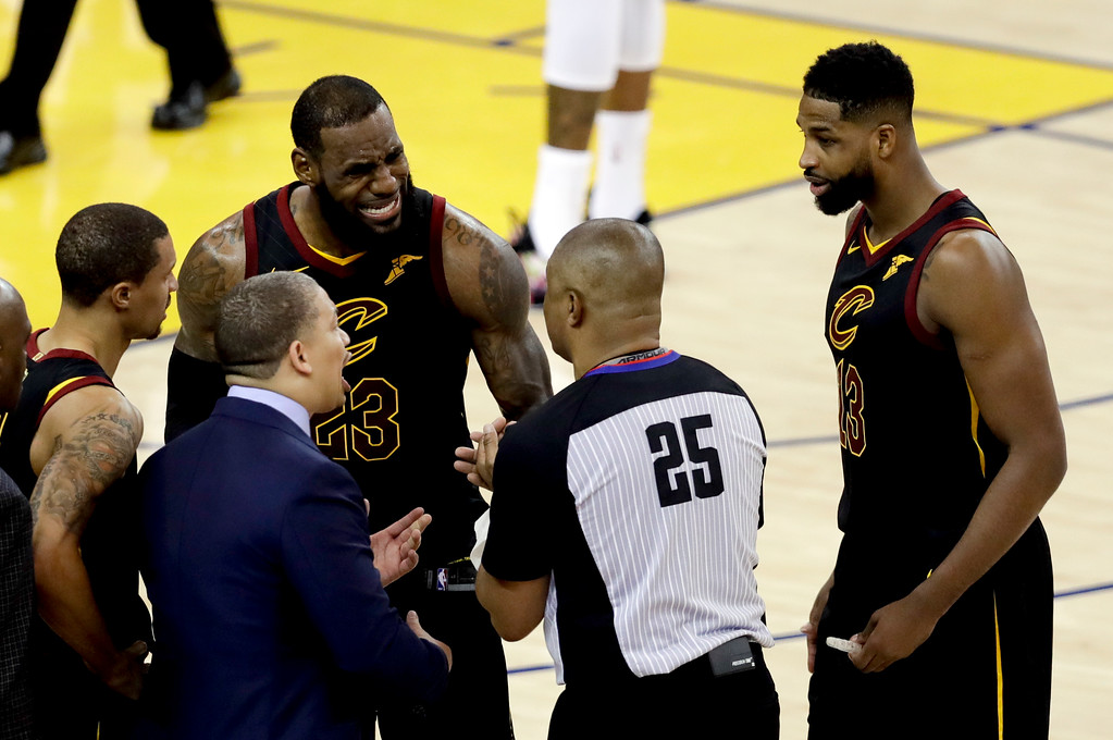 . Cleveland Cavaliers forward LeBron James (23) and head coach Tyronn Lue, bottom, talk with referee Tony Brothers (25) during the second half of Game 1 of basketball\'s NBA Finals against the Golden State Warriors in Oakland, Calif., Thursday, May 31, 2018. (AP Photo/Marcio Jose Sanchez)