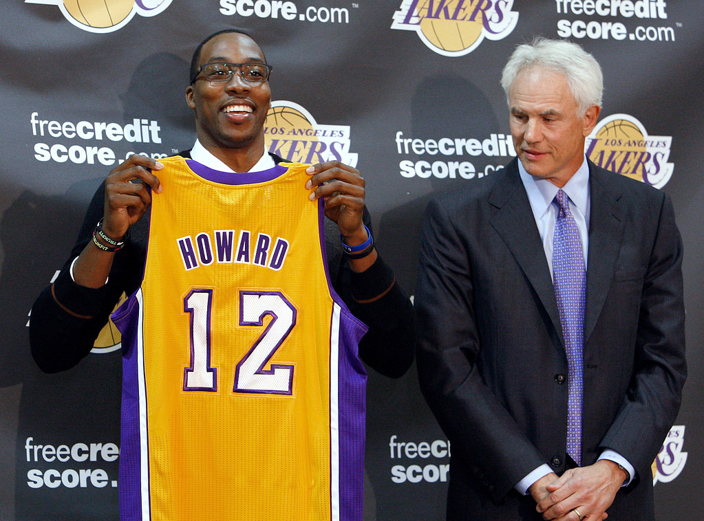 . Center Dwight Howard, newly acquired by the Los Angeles Lakers from the Orlando Magic, poses with his Lakers jersey with Lakers general manager Mitch Kupchak, at a news conference at the NBA basketball team\'s headquarters in El Segundo, Calif. (AP Photo/Reed Saxon)