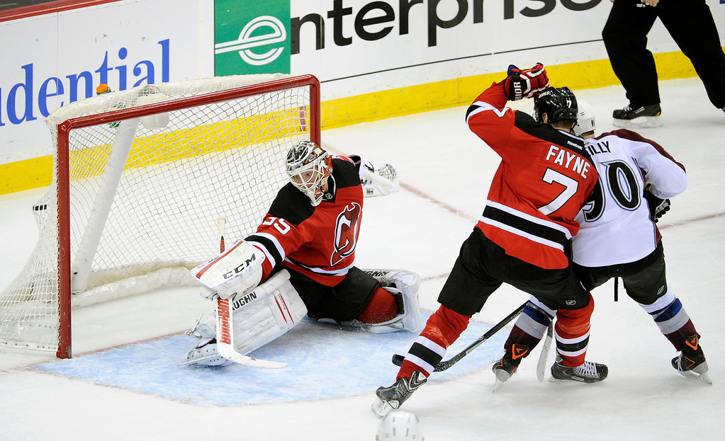 . New Jersey Devils Mark Fayne (7) checks Colorado Avalanche\'s Ryan O\'Reilly, as O\'Reilly tips the puck into the net for the game-winning goal past Devils goaltender Cory Schneider, left, during the overtime period of an NHL hockey game, Monday, Feb. 3, 2014, in Newark, N.J. The Avalanche defeated the Devils 2-1. (AP Photo/Bill Kostroun)