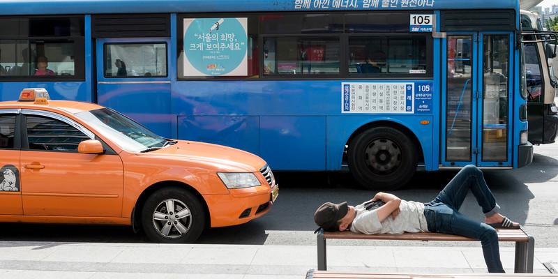 Man resting on bench at roadside, Seoul, South Korea