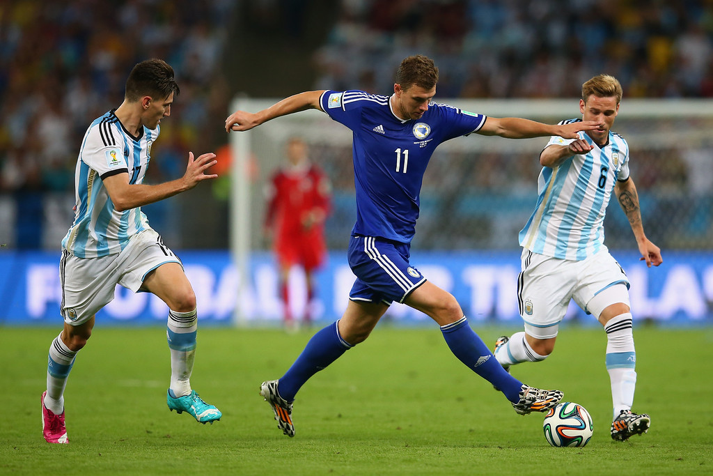 . Edin Dzeko of Bosnia and Herzegovina controls the ball against Federico Fernandez (L) and Lucas Biglia of Argentina during the 2014 FIFA World Cup Brazil Group F match between Argentina and Bosnia-Herzegovina at Maracana on June 15, 2014 in Rio de Janeiro, Brazil.  (Photo by Julian Finney/Getty Images)