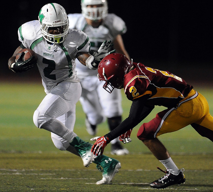 . Monrovia\'s Kurt Scoby (2) pushes away from Arcadia\'s Robbie Hiller (2) as he runs for 45 yard touchdown in the first half of a prep football game at Arcadia High School in Arcadia, Calif. on Friday, Sept. 13, 2013.   (Photo by Keith Birmingham/Pasadena Star-News)