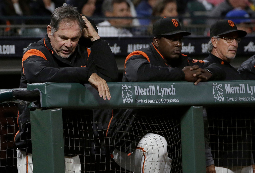 . San Francisco Giants manager Bruce Bochy, from left, watches from the dugout with batting coach Hensley Meulens and bench coach Ron Wotus during a baseball game against the Cleveland Indians in San Francisco, Tuesday, July 18, 2017. (AP Photo/Jeff Chiu)