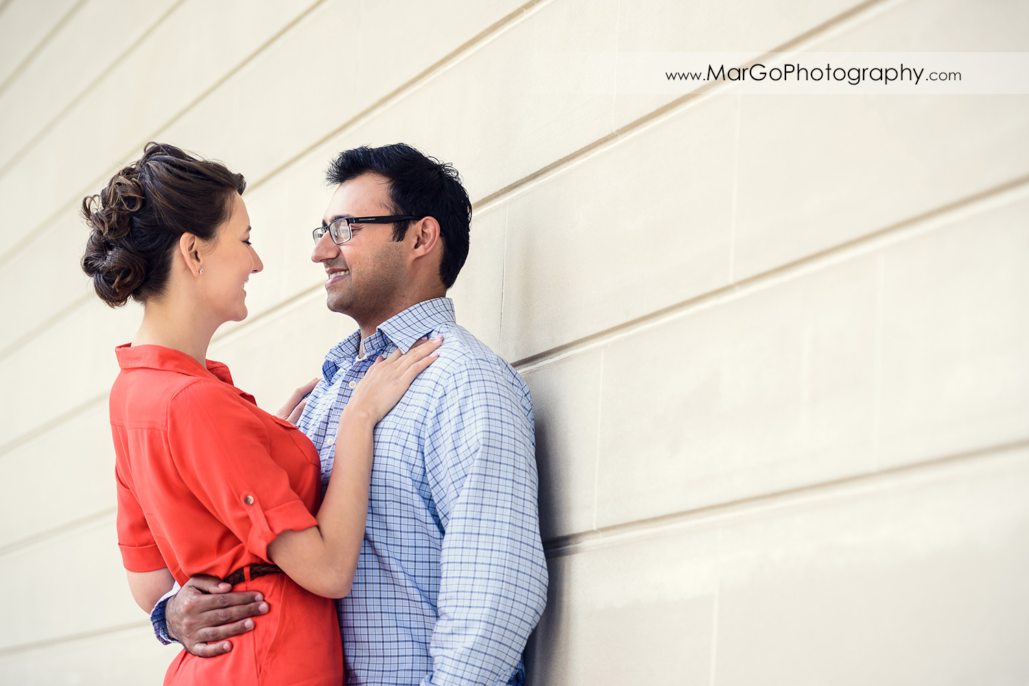 portrait of woman in red dress and man in blue shirt looking at each other during engagement session at San Francisco Legion of Honor