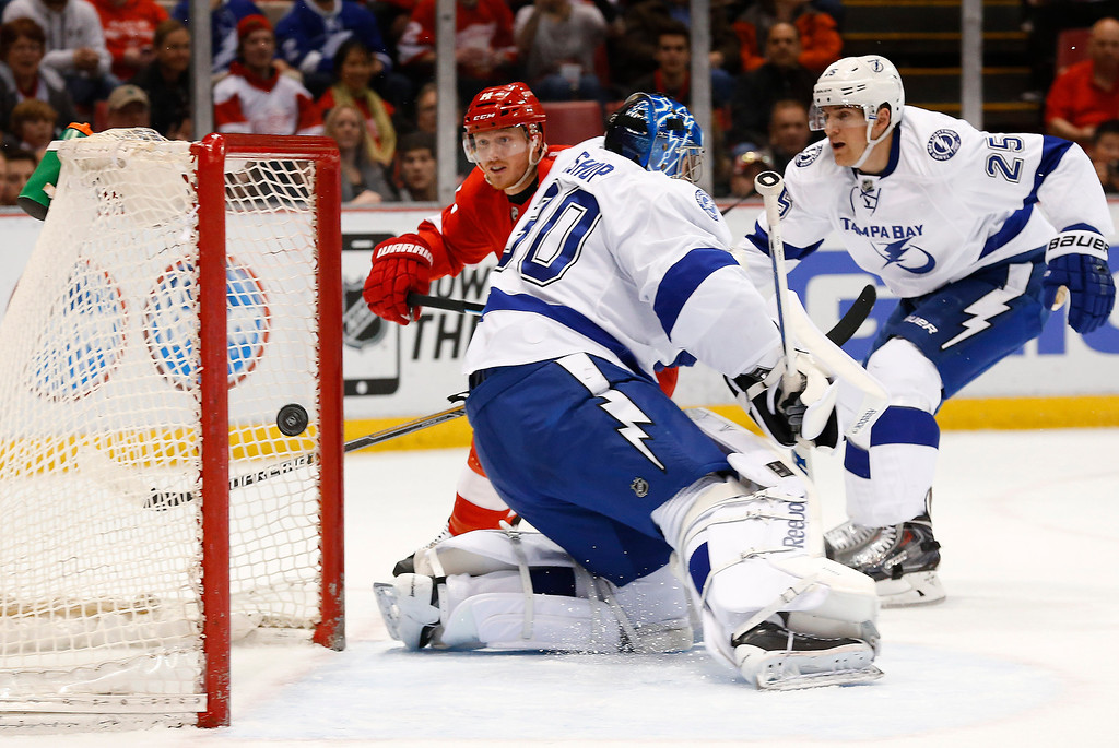 . Detroit Red Wings center Gustav Nyquist, left, scores against Tampa Bay Lightning goalie Ben Bishop (30) as Matt Carle (25) defends in the second period of an NHL hockey game in Detroit, Saturday, March 28, 2015. (AP Photo/Paul Sancya)