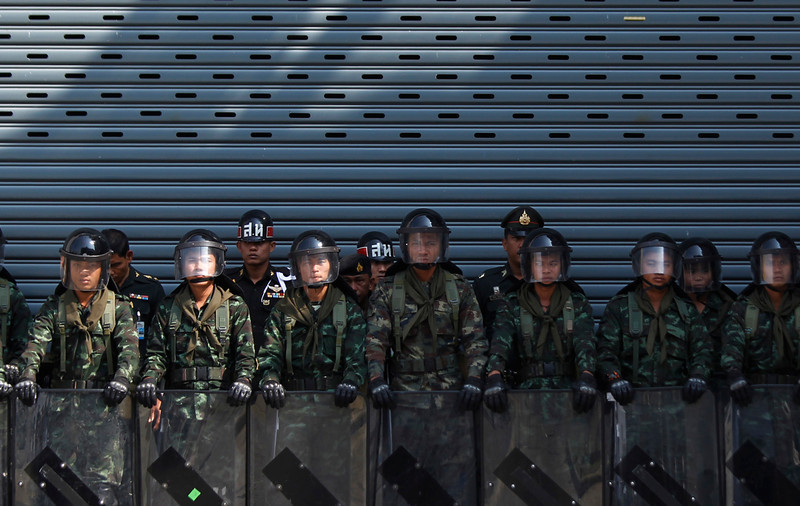 . Thai army soldiers stand guard as anti-government protesters rally outside the Permanent Secretary of Defense in Bangkok, Thailand, Wednesday, Jan. 22, 2014. Gunmen shot and wounded a top leader of a major pro-government movement in northern Thailand on Wednesday, and demonstrators pushing to overthrow the prime minister defied the start of a state of emergency imposed in the capital to cope with the nation\'s increasingly bloody political crisis. (AP Photo/Wally Santana)
