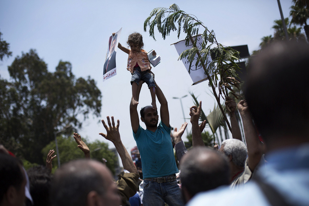 . An Egyptian holds up a child holding a poster supporting Egypt\'s Islamist President Mohammed Morsi during a rally near Cairo University in Giza, Egypt, Tuesday, July 2, 2013.  (Associated Press: Manu Brabo)