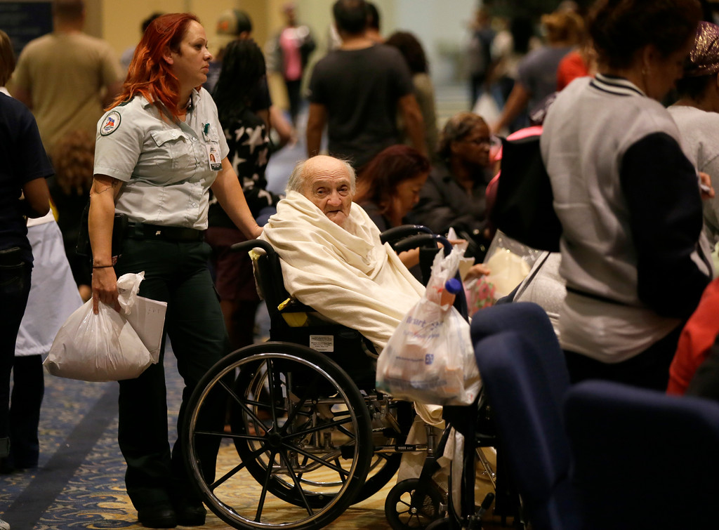. Evacuee Teddy Gifford, 90, waits for a medical evaluation with first responder Veronica Garza at the Lakewood Church in Houston, Texas, Tuesday, Aug. 29, 2017. Joel Olsteen and his congregation have set up their church as a shelter for evacuees from the flooding by Tropical Storm Harvey. (AP Photo/LM Otero)
