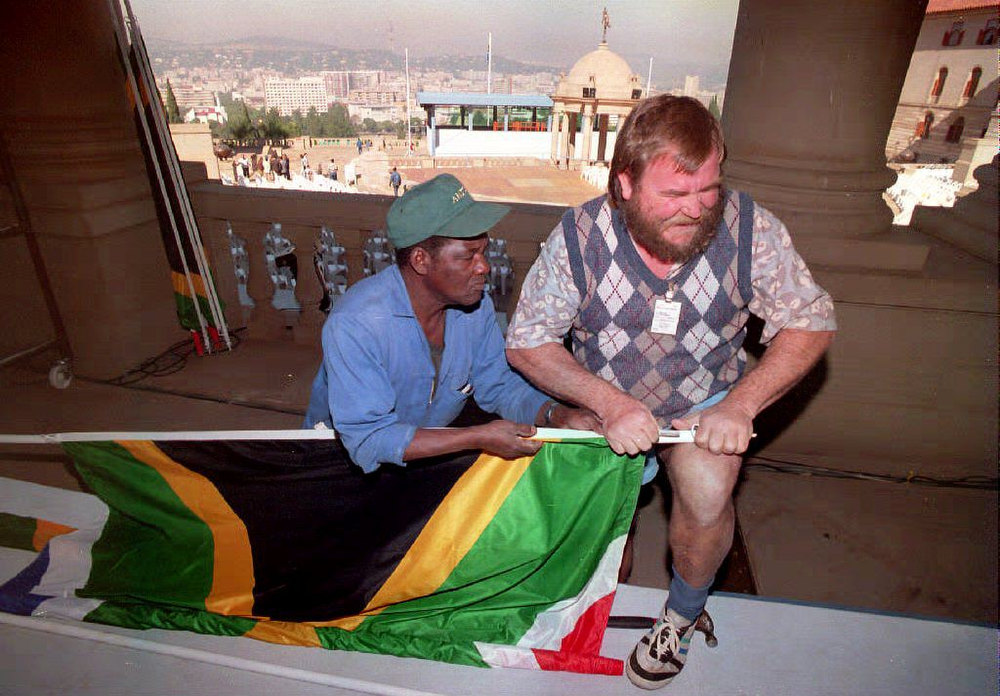 Description of . South African workers prepare to mount the new South African flag in Pretoria 06 May 1994, at the Union Building in preparation for the inauguration of President-designate Nelson Mandela on 10 May 1994. (Photo credit should read WALTER DHLADHLA/AFP/Getty Images)