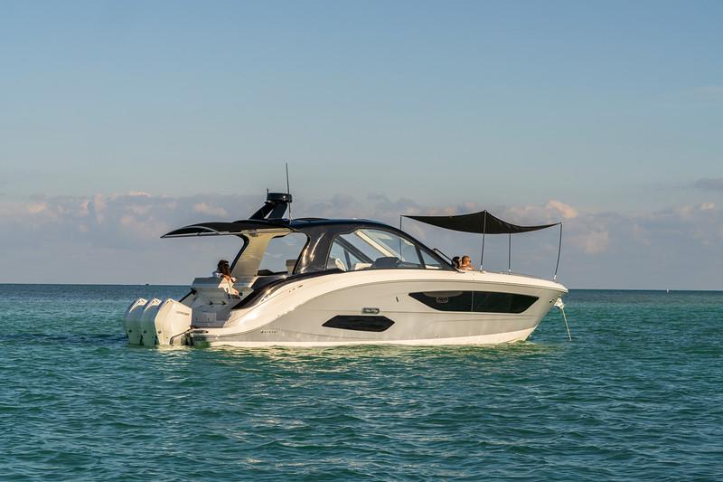 2021-Sundancer-370-Outboard-DAO370-lifestyle-starboard-stern-three-quarter-couple-bow-sunshade-cockpit-sureshade-05683.jpg
