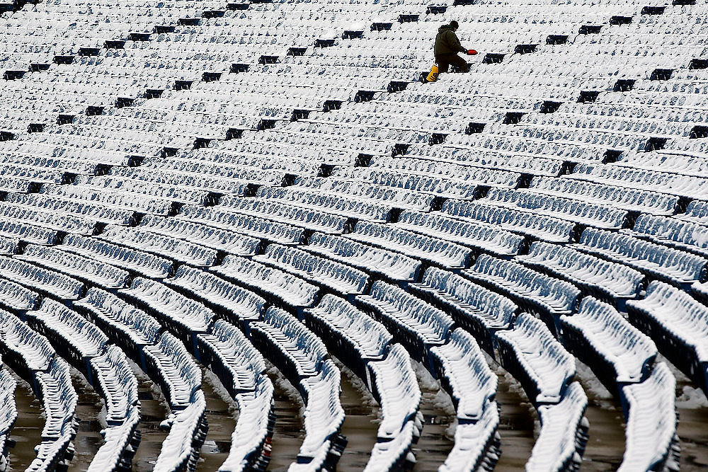 Description of . A worker spreads salt to melt ice and clear snow from the stands at Ralph Wilson Stadium before an NFL football game between the New York Jets and Buffalo Bills, Sunday, Dec. 30, 2012, in Orchard Park, N.Y. (AP Photo/Mel Evans)