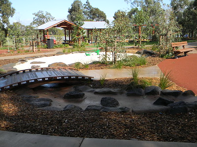 timber bridge over water channel to naturalistic sandpit with boulder edging and digger and bbq shade structure and bench seat