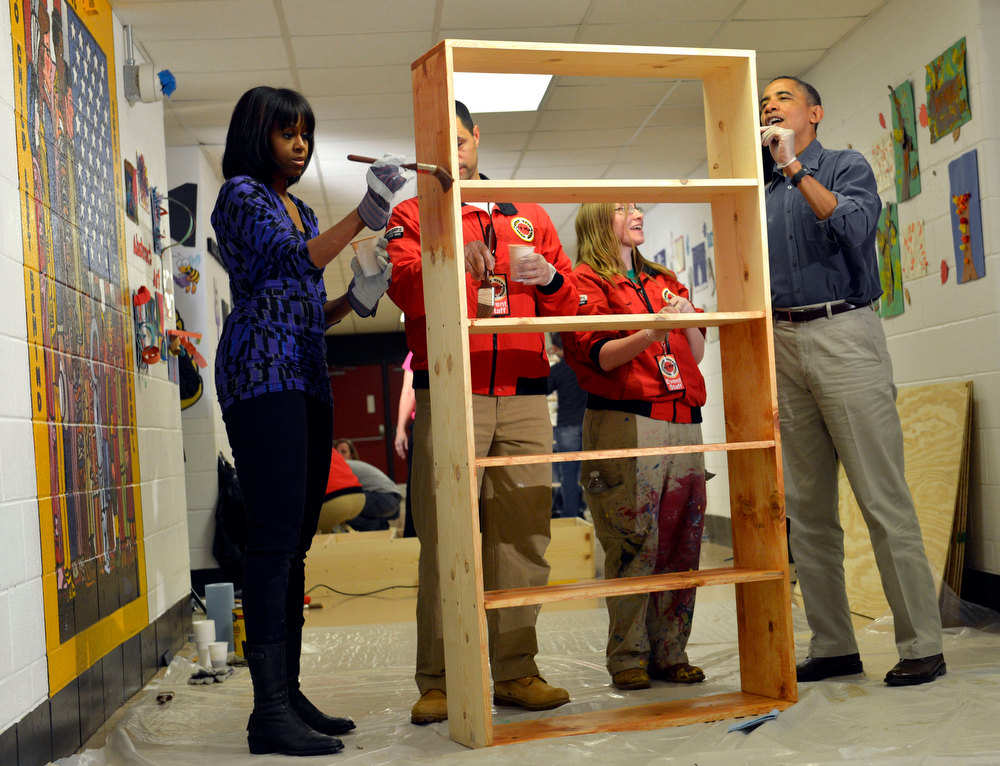 Description of . President Barack Obama, right, first lady Michelle Obama, left,  City Year Executive Director Jeff Franco, City Year and City Year employee Sheri Fisher, second from right, stain a bookshelf at Burrville Elementary School in Washington, Saturday, Jan. 19, 2013, as the first family participated in a community service project for the National Day of Service as part of the 57th Presidential Inauguration. (AP Photo/Susan Walsh)