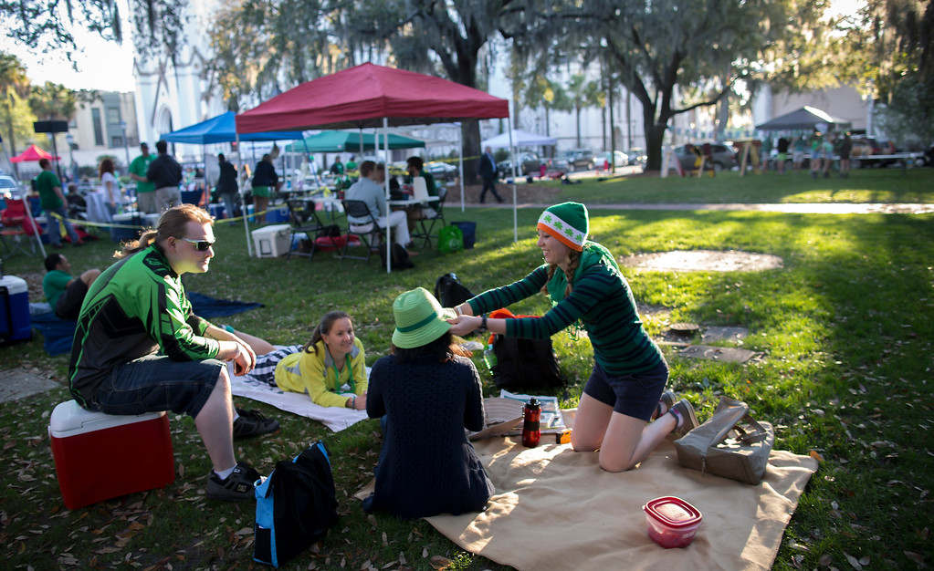 . Maeve Snyder, right, places a green hat on her friend Cara Lin, center, in one of the historic squares before the start of the St. Patrick\'s Day parade, Tuesday, March 17, 2015, in Savannah, Ga. Savannah has been celebrating St. Patrick\'s Day for 191 years, there have been at least six years without a parade. (AP Photo/Stephen B. Morton)