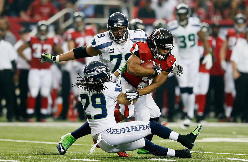 . Jacquizz Rodgers #32 of the Atlanta Falcons breaks the tackle of  Red Bryant #79 and  Earl Thomas #29 of the Seattle Seahawks during the NFC Divisional Playoff Game at Georgia Dome on January 13, 2013 in Atlanta, Georgia.  (Photo by Kevin C. Cox/Getty Images)