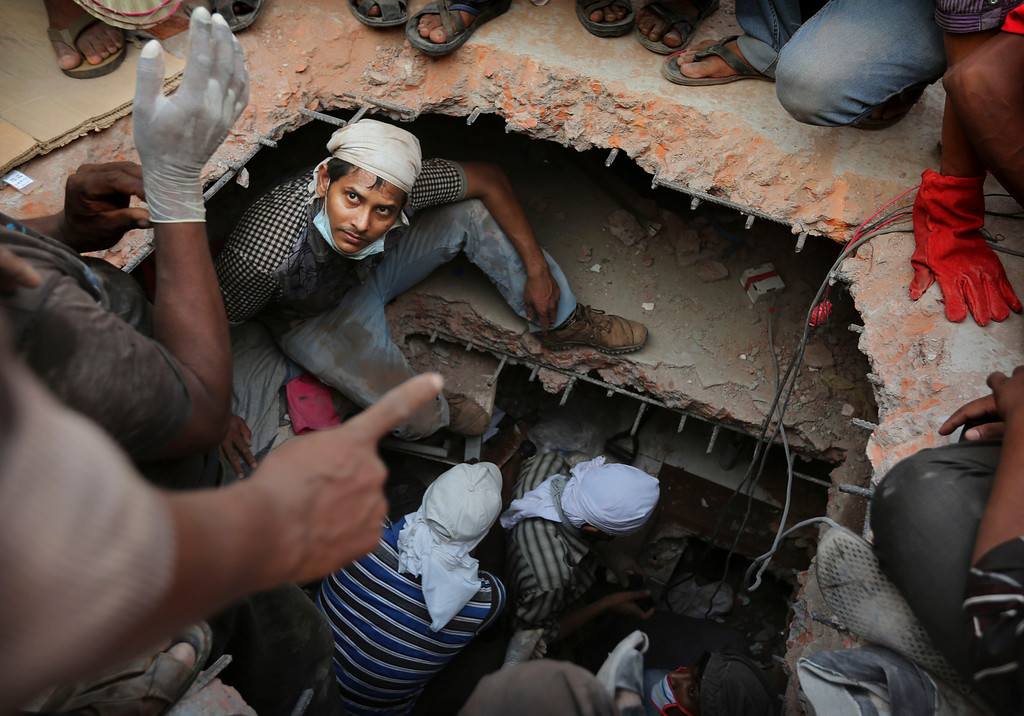 . A Bangladeshi rescuer looks out from a hole cut in the concrete as he looks for survivors at the site of a building that collapsed Wednesday in Savar, near Dhaka, Bangladesh, Thursday, April 25, 2013. (AP Photo/Kevin Frayer)