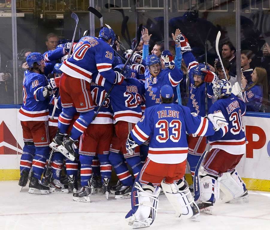 . The New York Rangers mob teammate Martin St. Louis after he scored the winning goal during overtime in Game 4 of the NHL hockey Stanley Cup playoffs Eastern Conference finals against the Montreal Canadiens, Sunday, May 25, 2014, in New York. The Rangers defeated the Canadiens in overtime 3-2. (AP Photo/Seth Wenig)