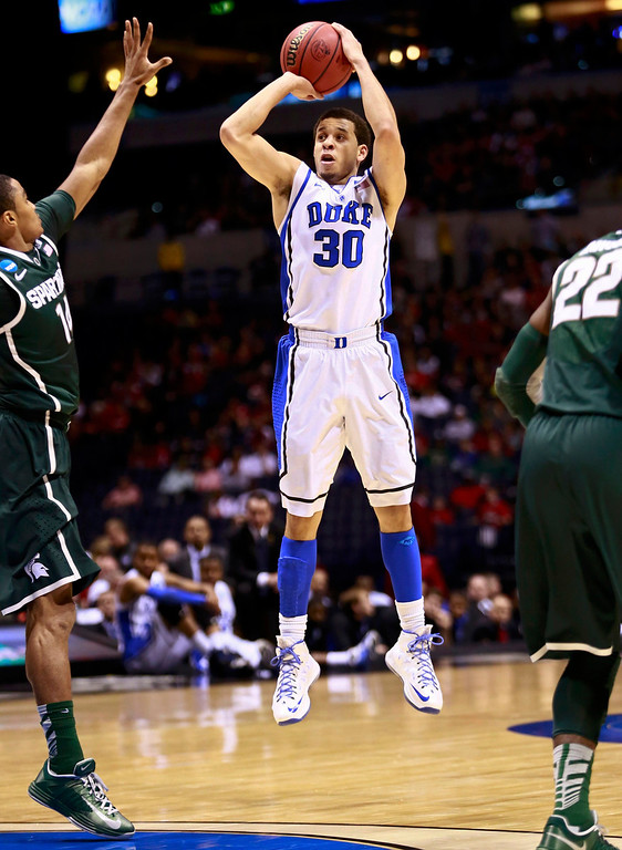 . Duke Blue Devils guard Seth Curry (30) shoots a three-point shot over Michigan State Spartans guard Gary Harris (14) during their Midwest Regional NCAA men\'s basketball game in Indianapolis, Indiana, March 29, 2013. REUTERS/Brent Smith