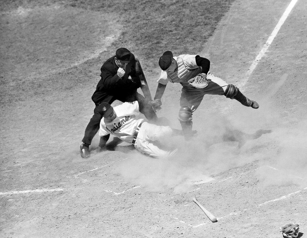 . Larry Doby of the Cleveland Indians is out at home plate as Baltimore Orioles catcher Clint Courtney tags him in the second inning in Cleveland on May 22, 1945. George Strickland grounded to third baseman Vern Stephens who threw to Courtney to cut off the run. The umpire calling the play is Lester C. Chylak. (AP Photo)