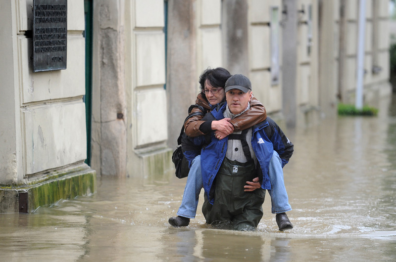 . A volunteer carries a woman from her working place out of the old town of Passau, southern Germany, Monday, June 3, 2013. Flooding has spread across a large area of central Europe following heavy rainfall in recent days. (AP Photo/dpa, Andreas Gebert)