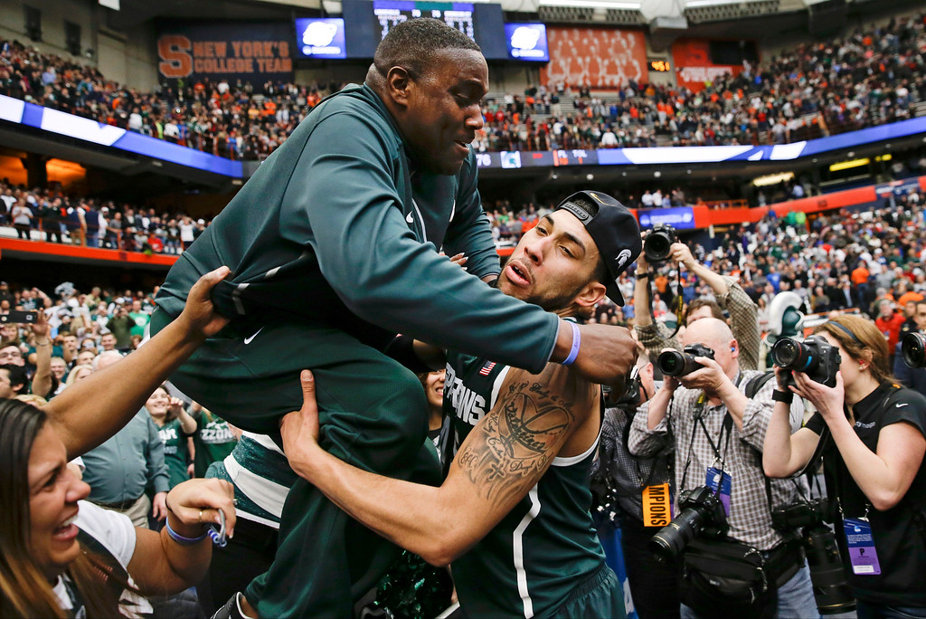 . Michigan State\'s Denzel Valentine, right, greets someone from the audience after Michigan State\'s 76-70 win over Louisville in an NCAA men\'s college basketball tournament regional final, Sunday, March 29, 2015, in Syracuse, N.Y. (AP Photo/Seth Wenig)