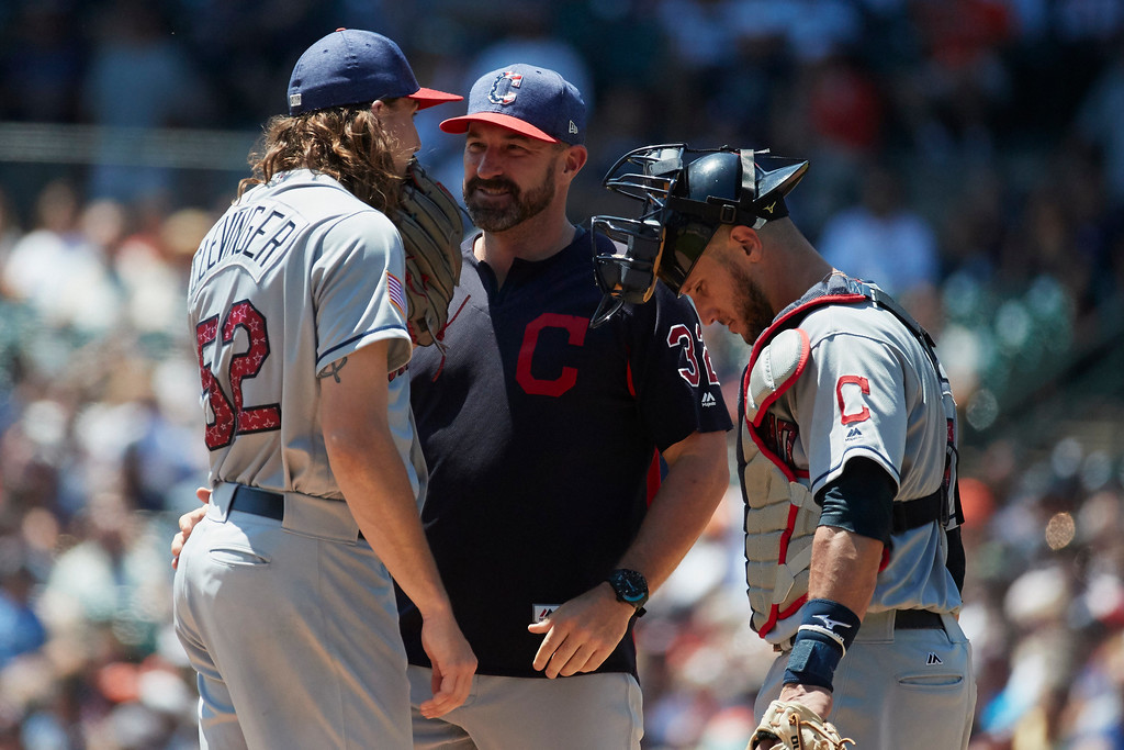 . Cleveland Indians pitching coach Mickey Callaway, center talks to starting pitcher Mike Clevinger and catcher Yan Gomes during the first inning of a baseball game against the Detroit Tigers in Detroit, Sunday, July 2, 2017. (AP Photo/Rick Osentoski)