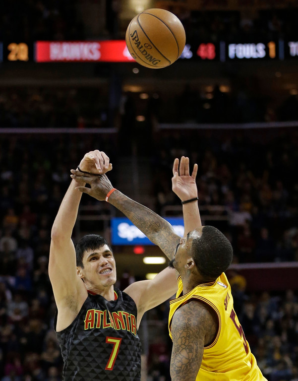 . Atlanta Hawks\' Ersan Ilyasova (7), from Turkey, passes over Cleveland Cavaliers\' J.R. Smith (5) in the first half of an NBA basketball game, Friday, April 7, 2017, in Cleveland. (AP Photo/Tony Dejak)