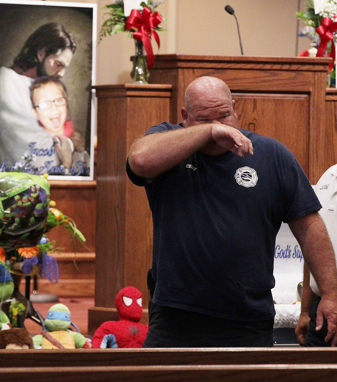 . Townville Fire Chief Billy McAdams wipes tears during a superhero-themed funeral service for Jacob Hall at Oakdale Baptist Church on Wednesday, Oct. 5, 2016, in Townville, S.C. A 14-year-old boy killed his own father, then drove to Townville Elementary and fired on two children and a teacher as recess began. Jacob died Saturday. (Ken Ruinard/The Independent-Mail via AP, Pool)