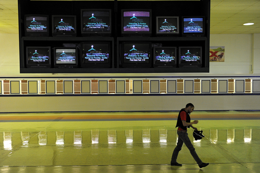 . A passerby walks past betting windows two days prior to the 139th Preakness Stakes at Pimlico Race Course on May 15, 2014 in Baltimore, Maryland. (Photo by Patrick Smith/Getty Images)