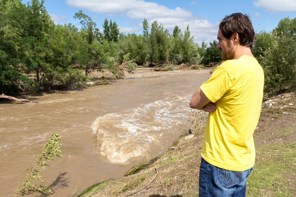 . Andy Frith, who works in Longmont, observes the rapidly flowing St. Vrain Creek in the city on Monday, September 16, 2013. As evident by the flattened grass, the water level at one point covered all the exposed land in this picture. Photo by Arien Talabac
