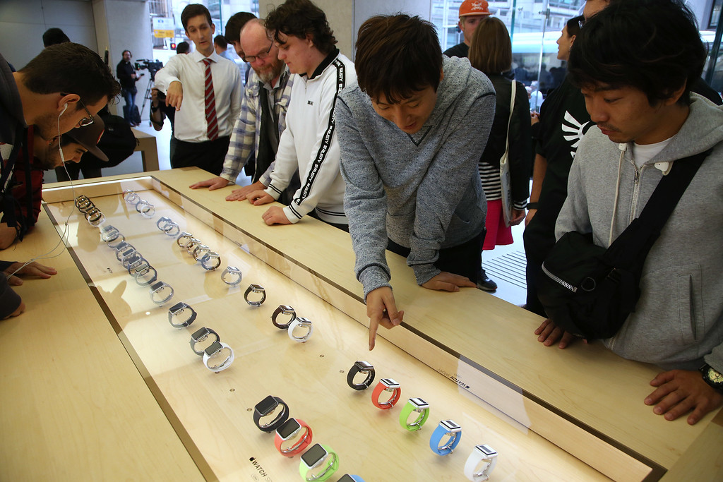 . Customers look at a selection of Apple Watches as the public have its first chance to see, touch and pre-order the watch in Sydney, Friday, April 10, 2015. Prices start at $349, but can go as high as $17,000 for a luxury edition in gold. (AP Photo/Rick Rycroft)
